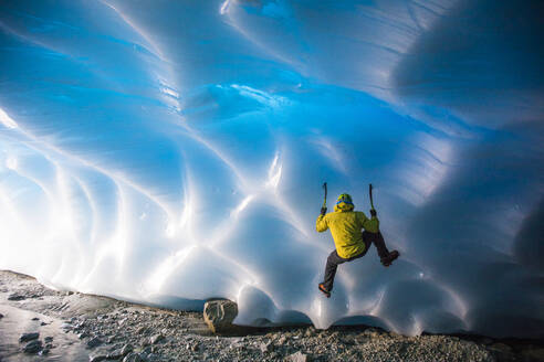 Mountaineer ice climbing on glacial ice in ice cave. - CAVF77929