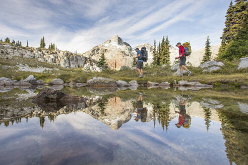 Side view and reflection of backpackers hiking beside alpine lake. - CAVF77941