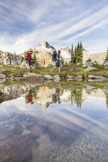 Side view and reflection of backpackers hiking beside alpine lake. - CAVF77944