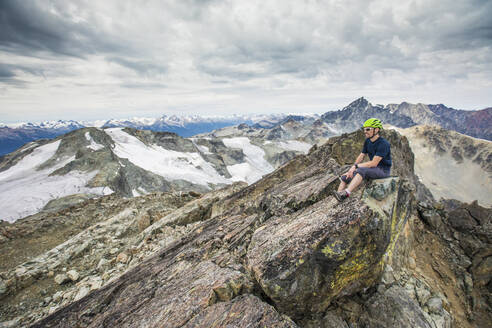 Climber sits on the rocky summit of a mountain. - CAVF77962