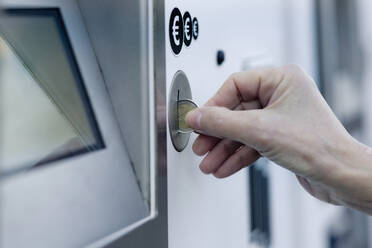 Woman's hand putting coin into pay machine - FLLF00439