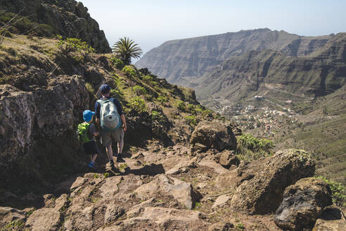 Back view of father and little son with backpacks walking on a hiking trail in the mountains, La Gomera, Canary Islands, Spain - IHF00293