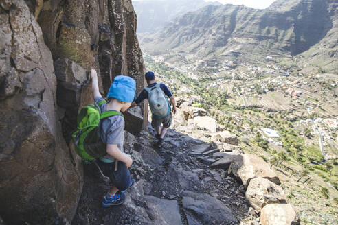 Back view of father and little son with backpacks on a hiking trail in the mountains, La Gomera, Canary Islands, Spain - IHF00296