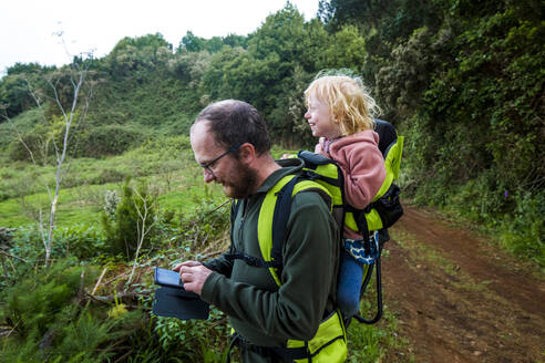 Father carrying his little daughter in a child carrier on a hiking trail, using smartphone, Canary Islands, La Palma, Spain - IHF00299