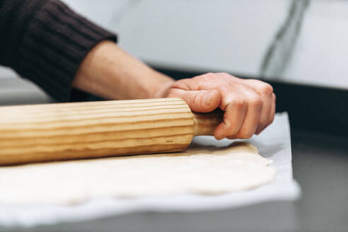 Woman rolling flat pizza dough - AMAF00018