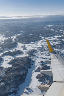 Finland, Wing of airplane flying over forested landscape in winter - AMAF00021
