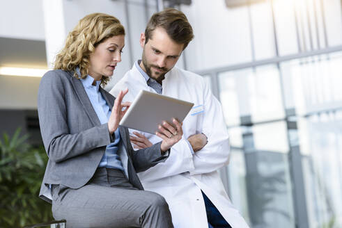 Businesswoman with tablet and doctor talking in hospital - BMOF00316