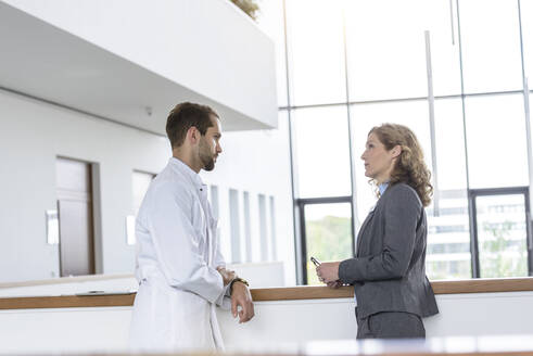 Businesswoman and doctor talking in hospital - BMOF00328