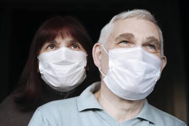 Portrait of senior couple wearing masks at home - EYAF00993