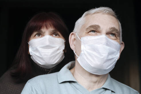 Portrait of senior couple wearing masks at home - EYAF00993