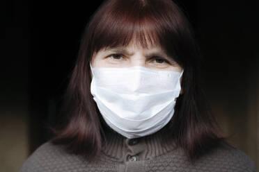 Portrait of senior women wearing mask at home - EYAF00996