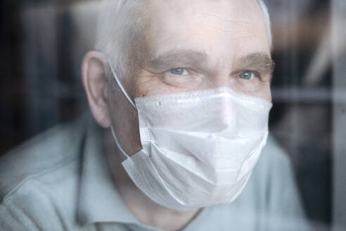 Portrait of senior man wearing a mask at home, looking out of the window - EYAF00999