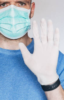 Portrait of man wearing mask and protective gloves - JCMF00495