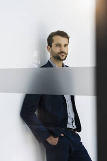 Portrait of young businessman leaning against wall looking at distance - BMOF00346