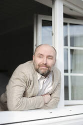 Portrait of relaxed mature man leaning out of window - VYF00085