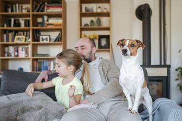 Father, little daughter and their dog spending time together on the couch - VYF00088
