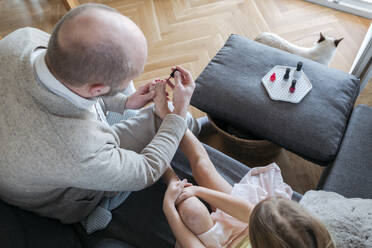 Father painting his daughter's toenails with red nail polish on the couch in living room, top view - VYF00091
