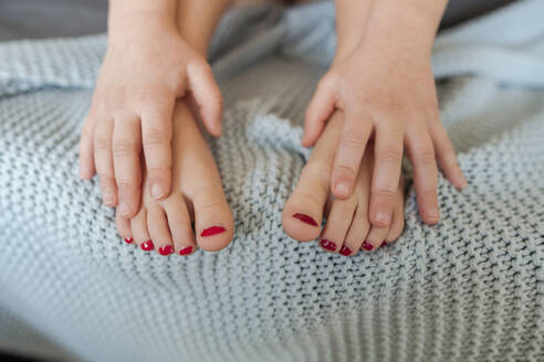 Little girl's hands touching her toes varnished with red nail polish - VYF00094