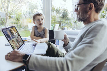 Little boy interrupting father's video conference at home - MFF05163