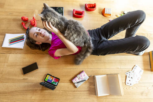 Girl lying on floor, cuddling cat, surrounded by play equipment - SARF04496