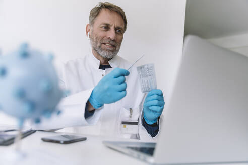 Scientist holding up lateral flow test device in video conference - MFF05191