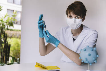Portrait of doctor preparing injection with Corona virus vaccine - MFF05221
