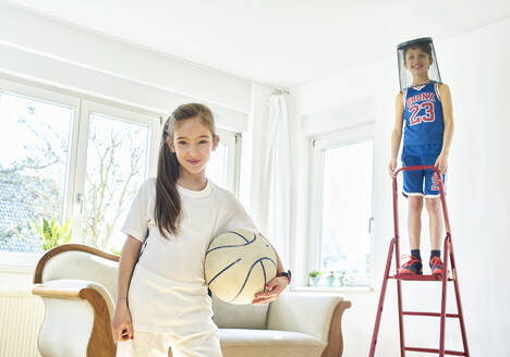 Portrait of girl and boy playing basketball in living room - DIKF00400
