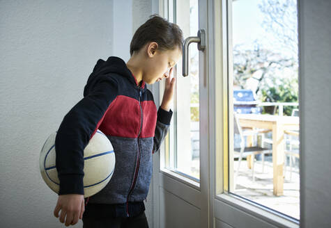 Sad boy with basketball leaning against the window - DIKF00406