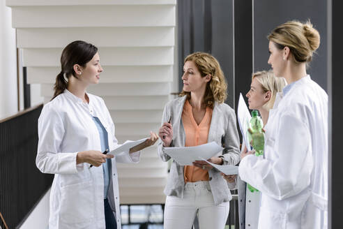 Businesswoman and female doctors having a work meeting in hospital - BMOF00350