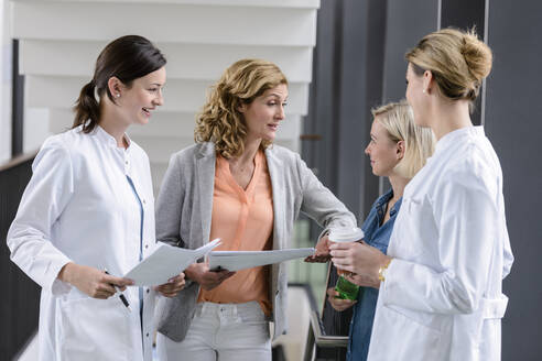 Businesswoman and female doctors having a work meeting in hospital - BMOF00353