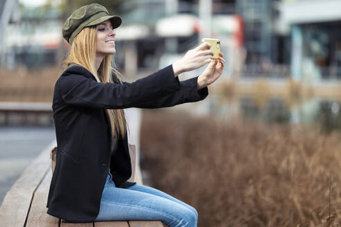 Smiling young woman sitting on a bench taking selfie with smartphone - JSRF00944