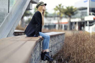 Blond young woman relaxing on a bench - JSRF00953