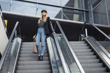 Blond young woman with bag and smartphone standing on an escalator looking at distance - JSRF00956
