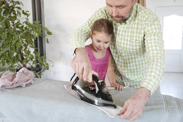Father and daughter ironing together at home - VYF00099
