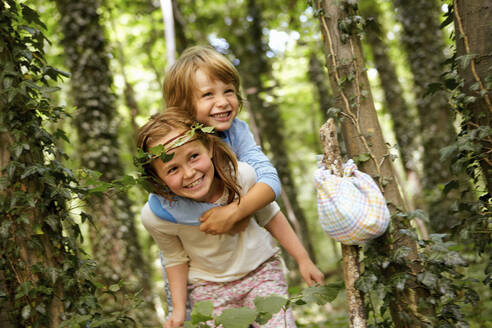 Girl carrying boy piggyback in forest - AUF00199