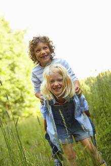 Girl carrying boy piggyback on a meadow - AUF00205