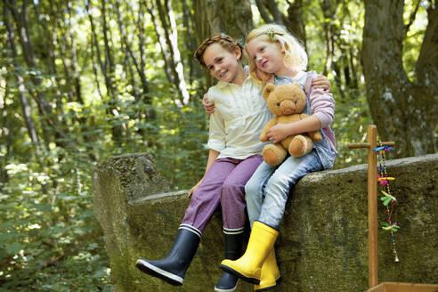 Children sitting on stone wall in forest - AUF00220