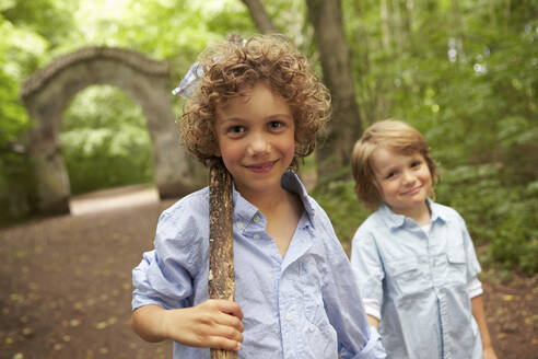 Portrait of boy with wood stick and friend in forest - AUF00226