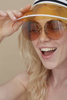 Portrait of happy young woman wearing sunglasses and sun visor - PGCF00074