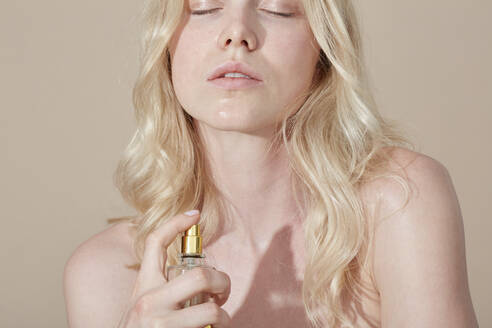 Blond young woman applying perfume - PGCF00077