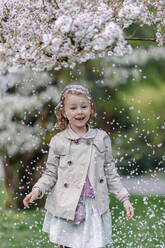 Portrait of happy little girl in a park standing under blossoming Japanese cherry tree - OGF00265