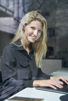 Portrait of smiling blond woman using laptop behind windowpane in office - PNEF02498