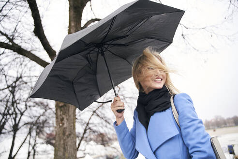 Smiling blond woman holding umbrella in storm - PNEF02504