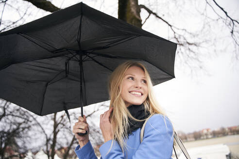 Smiling blond woman holding umbrella outdoors - PNEF02507