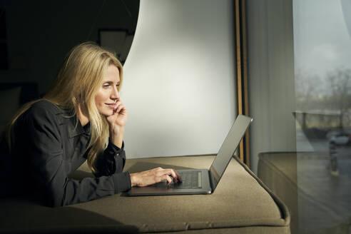 Blond woman lying on sofa using laptop - PNEF02510