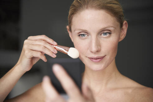 Portrait of beautiful woman applying make up - PNEF02528