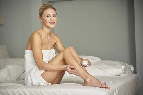 Portrait of smiling woman wrapped in a towel sitting on bed applying skin cream on her leg - PNEF02537