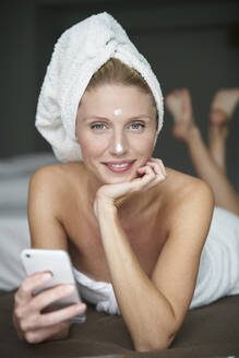 Portrait of beautiful woman with head wrapped in a towel holding smartphone on bed - PNEF02561