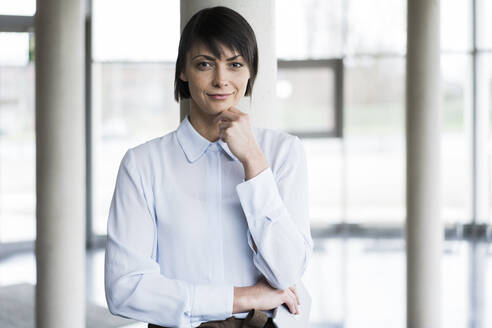 Serene businesswoman standing in bright office building - JOSEF00141