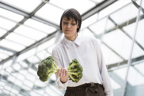 Businesswoman doing weight training with broccoli - JOSEF00186